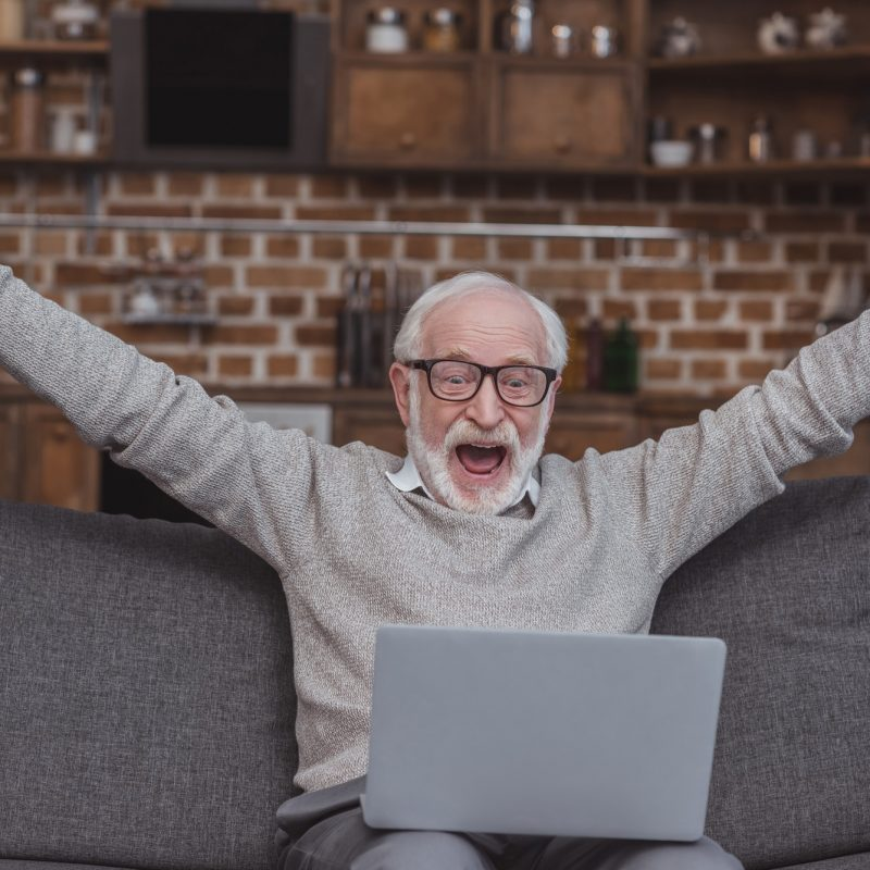 Happy grey hair man watching on laptop at home and celebrate win a bet with a gambling, soccer bet,