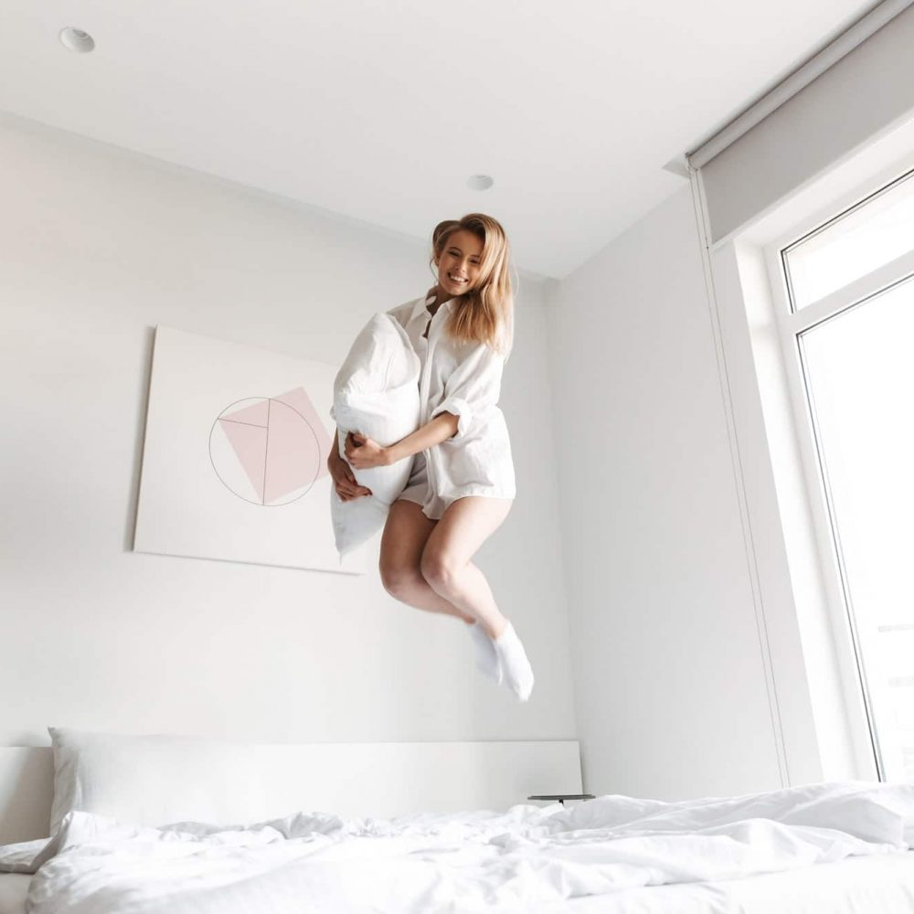 Happy pretty woman jumping with pillow