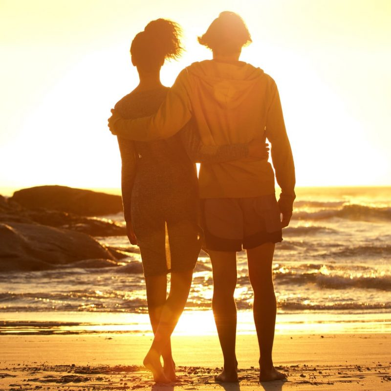 Man with arm around woman standing at the beach