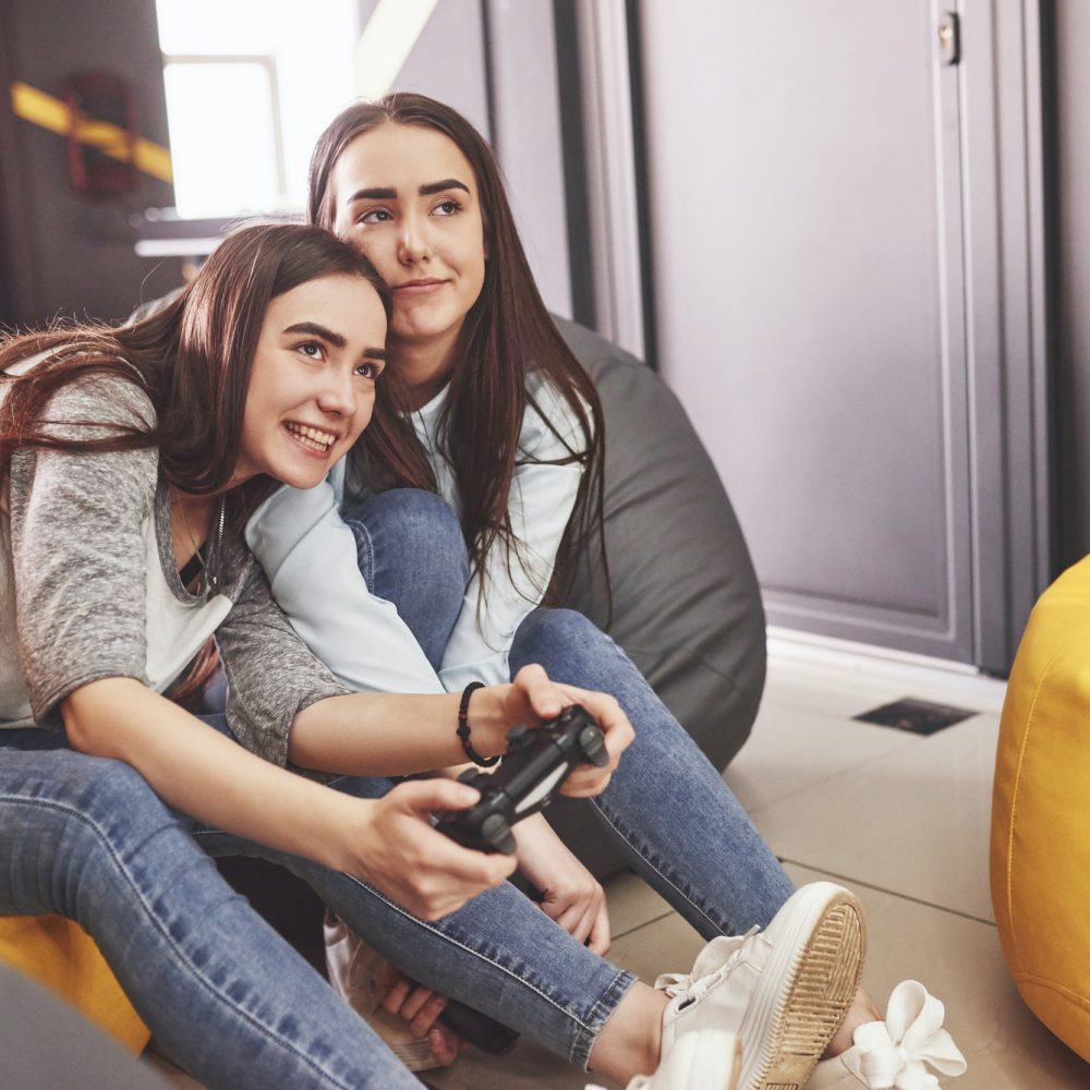 Twin sister sisters play on the console. Girls hold joysticks in their hands and have fun